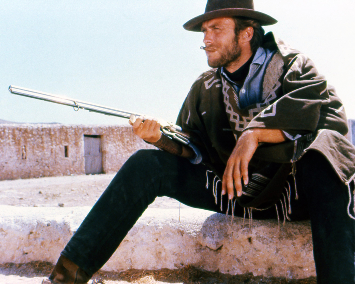 Clint Eastwood, US actor, smoking a cigar, wearing a brown hat and poncho, taking aim with a rifle in a publicity portrait issued for the film, 'A Fistful of Dollars', Spain, 1964.