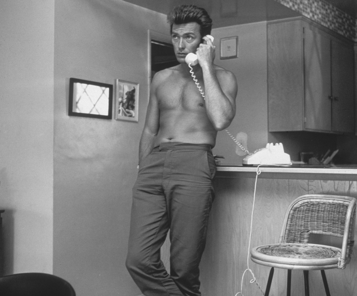 American actor Clint Eastwood leans against a kitchen counter, bare-chested, while speaking on the telephone from his home.