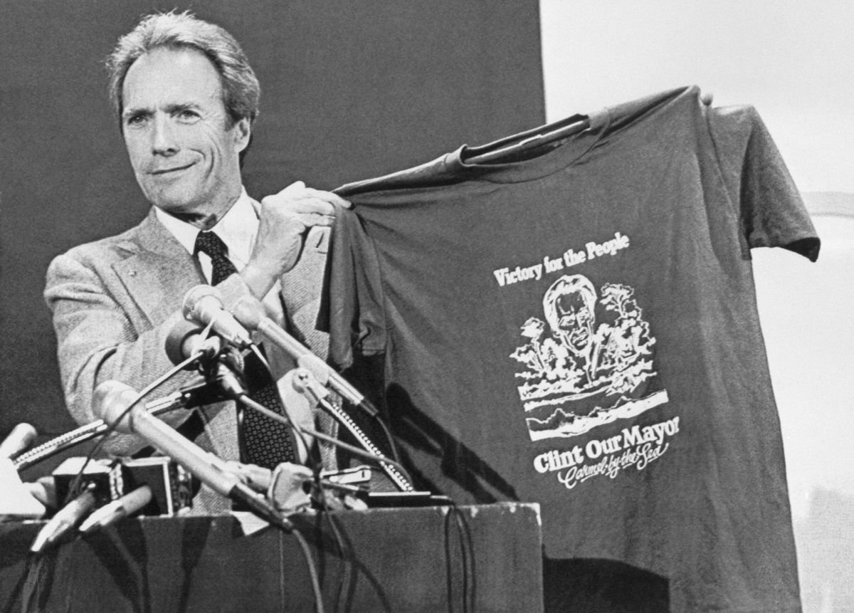 Clint Eastwood proudly holds up a t-shirt proclaiming him as the mayor of Carmel, California, during his acceptance speech on April 9, 1986.