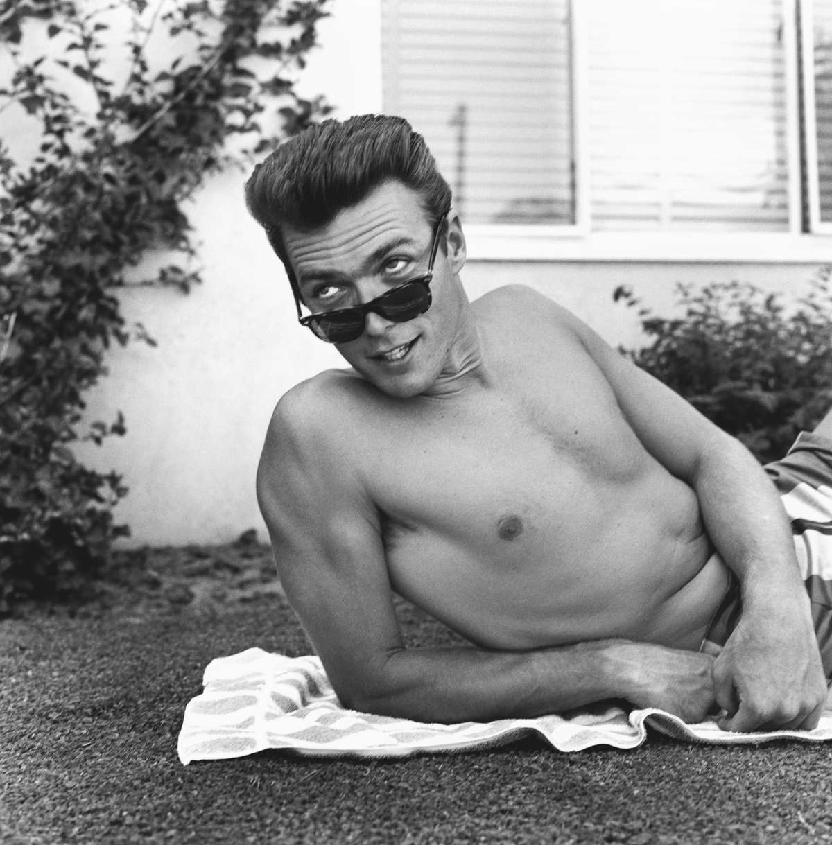 Actor Clint Eastwood lies on a towel and looks over his sunglasses at home on June 1, 1956 in Los Angeles, California.