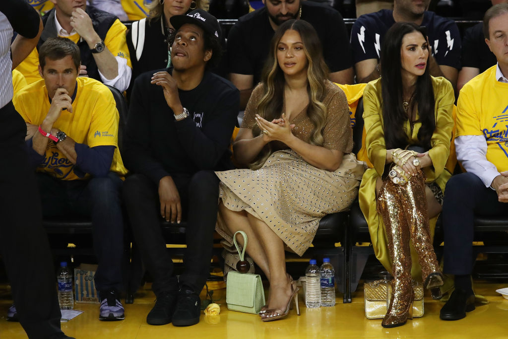 Beyonce sitting courtside with husband after woman leans over her