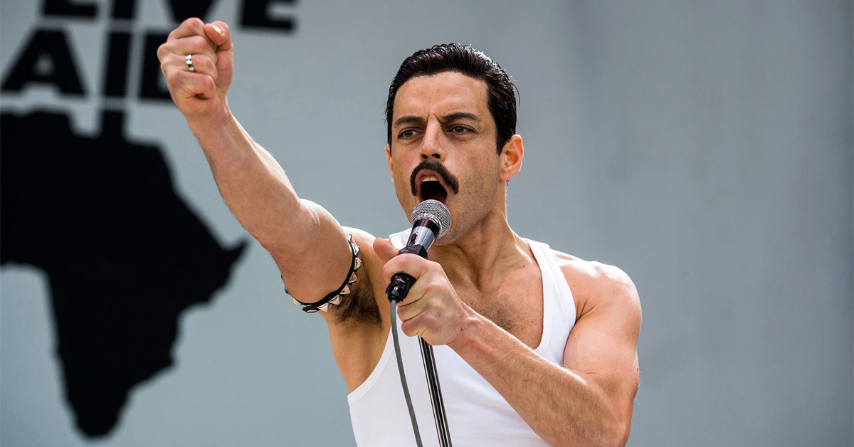 rami malek as freddie mercury in bohemian rhapsody singing at live aid with his fist in the air