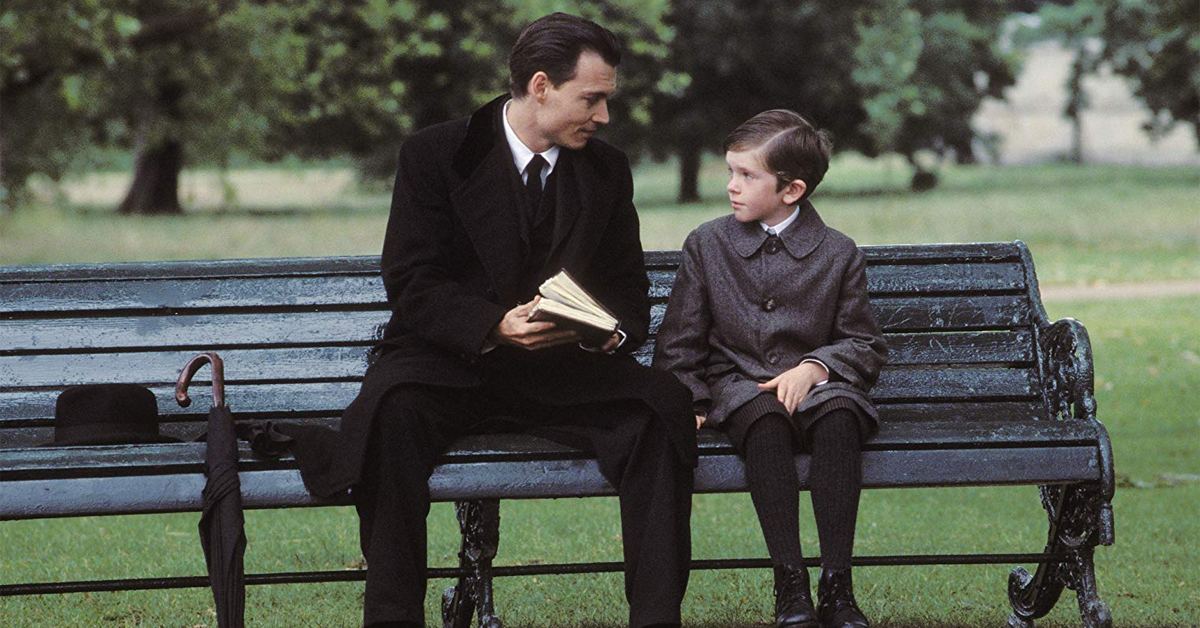 johnny depp holding a book and sitting on a bench with freddie highmore on finding neverland set