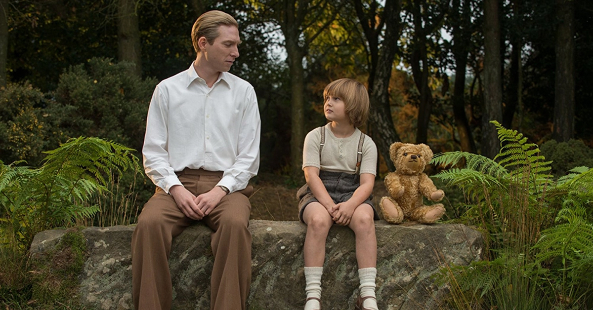 domhnall gleeson and will tilston sitting on a rock in a forest with a teddy bear