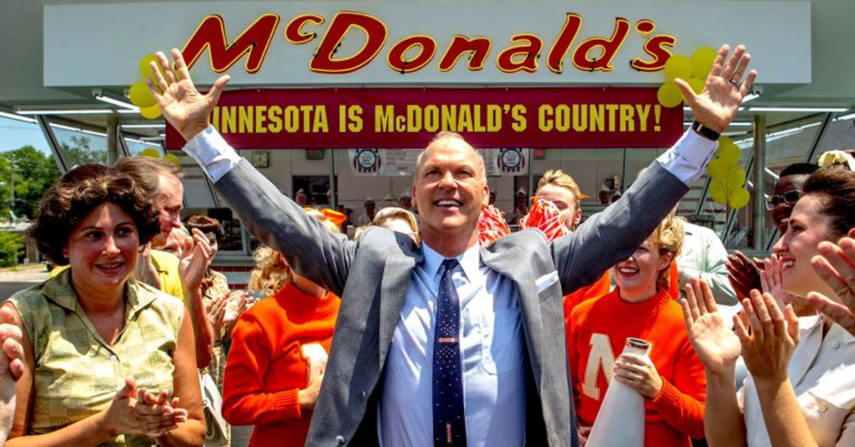 michael keaton holding his arms up in a crowd in front of a mcdonald's