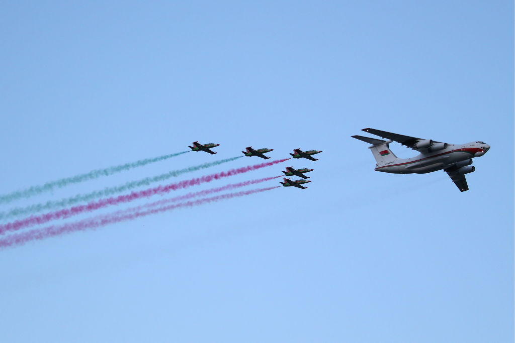 GettyImages-1153556449 An Ilyushin Il-76MD strategic airlifter and Aero L-39 Albatros trainer aircraft of the Belaya Rus aerobatic team leave a trail in the Belarusian national colours during a military parade