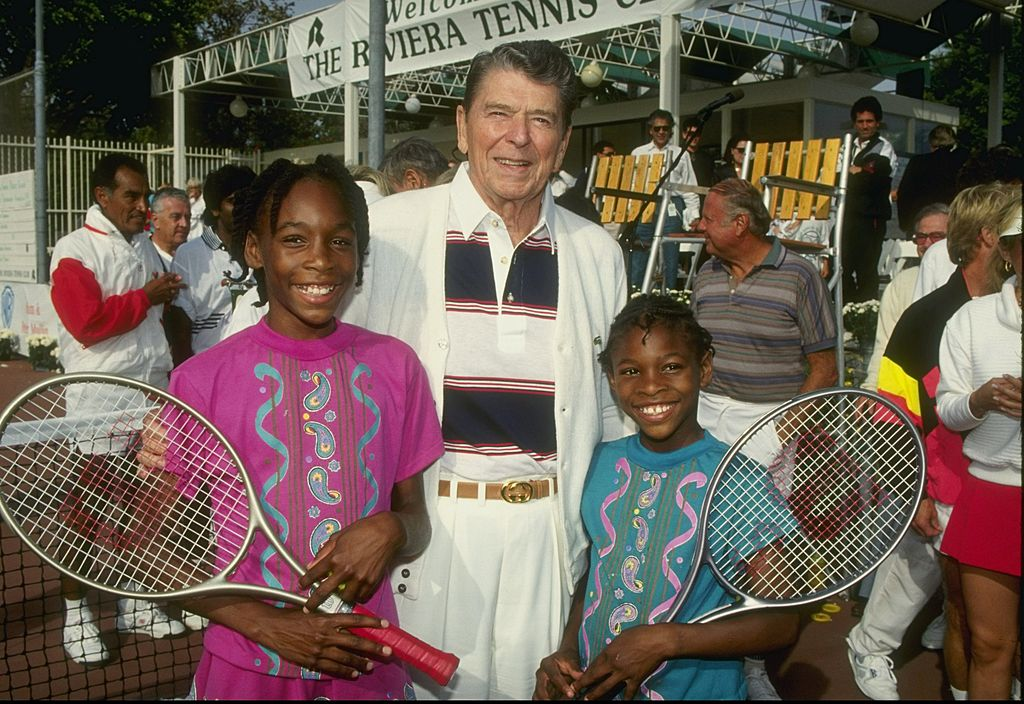 GettyImages-310235 1990: Serena Williams and her sister Venus Williams stand with former president Ronald Reagan at a tennis camp in Florida.