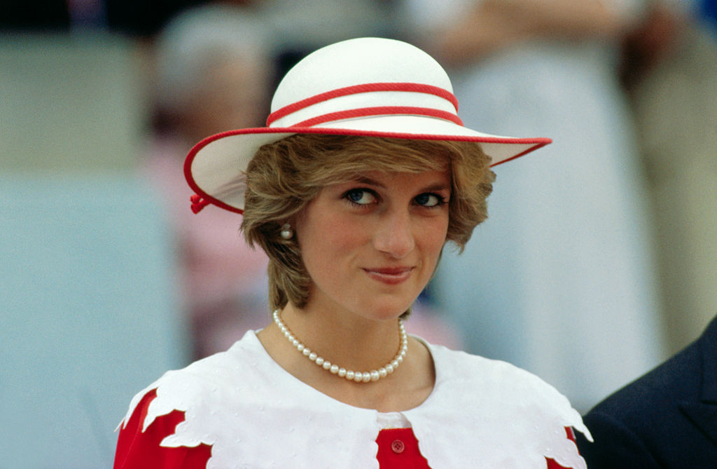 GettyImages-515207354 Diana, Princess of Wales, wears an outfit in the colors of Canada during a state visit to Edmonton, Alberta, with her husband.