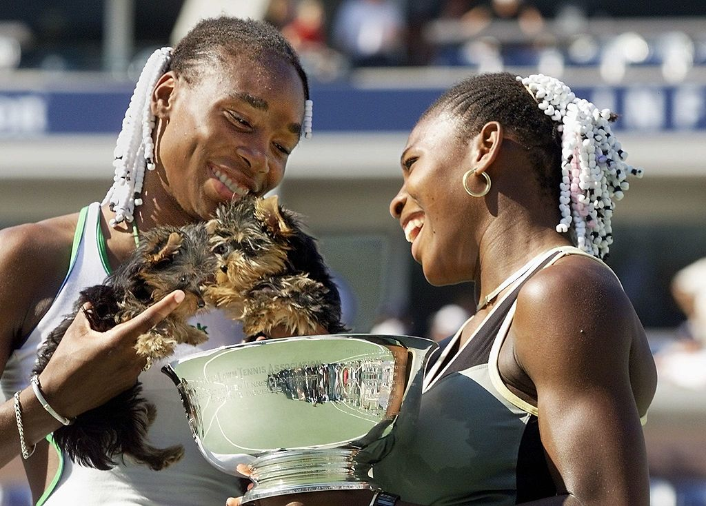 GettyImages-52034458 Serena Williams (R) and her sister Venus, of the US, hold their dogs and the US Open women's doubles trophy 12 September, 1999, at the US Open in Flushing Meadows.