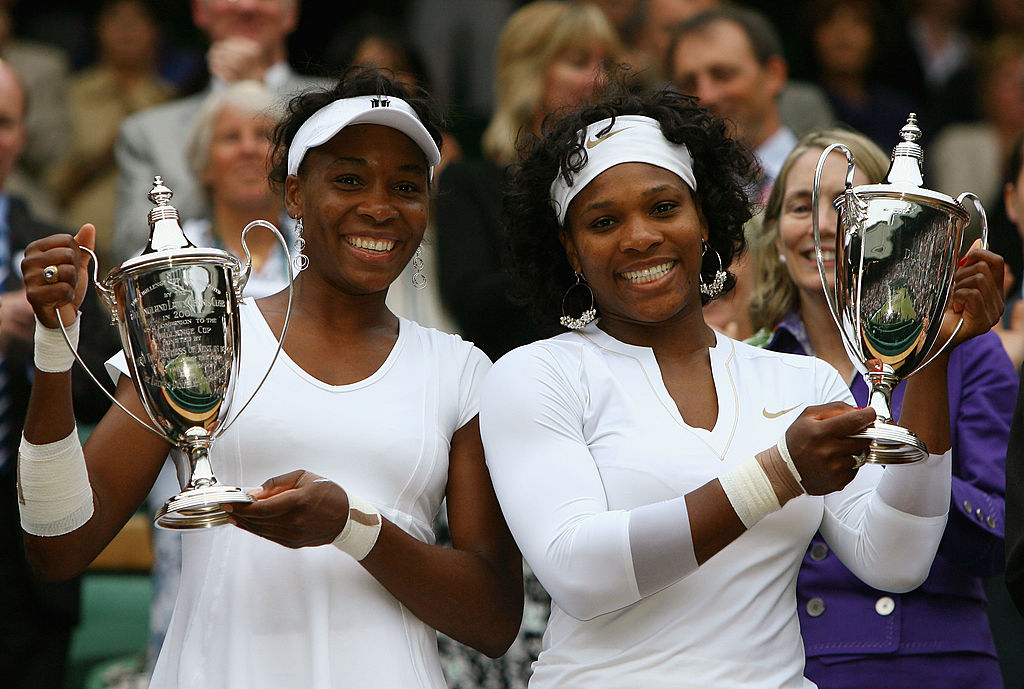 GettyImages-81831140 Venus Williams of United States and Serena Williams of United States celebrate with the trophy winning the women's doubles Final match