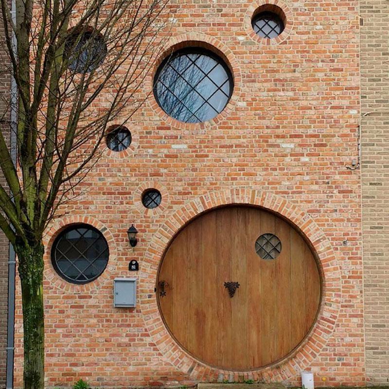 a house with circular windows and orange brick and a circle door