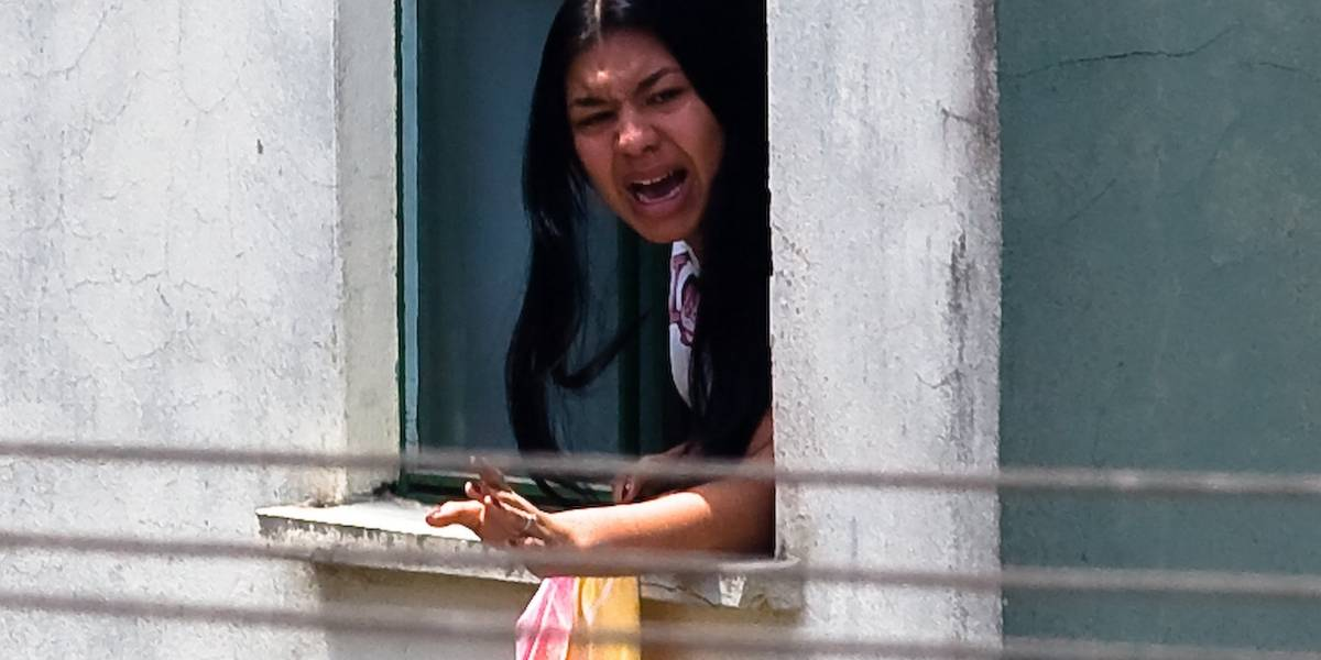 Eloá Pimentel leans out of a window, shouting presummably at police officers.