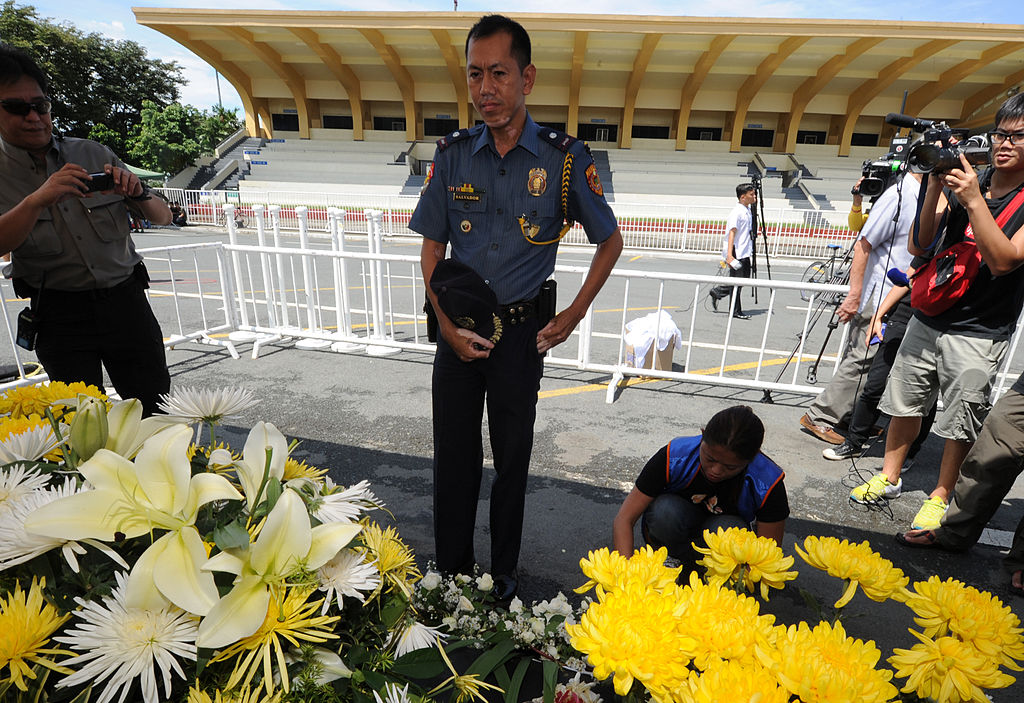 A Philippine chief inspector removes his hat while looking on to the ceremony held for victims of the bus hijacking.