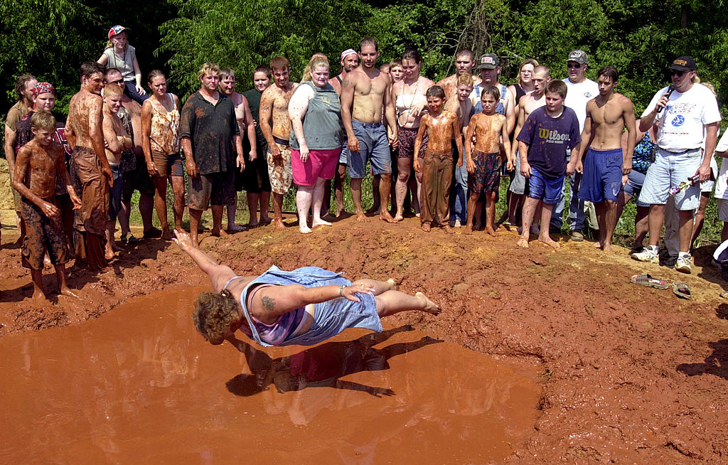 Woman belly flopping into mud