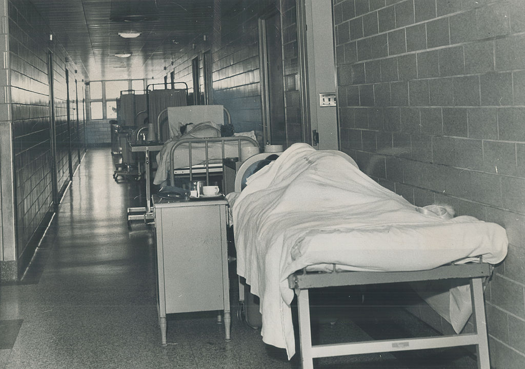 Patients rest in beds along a maternity ward hall.