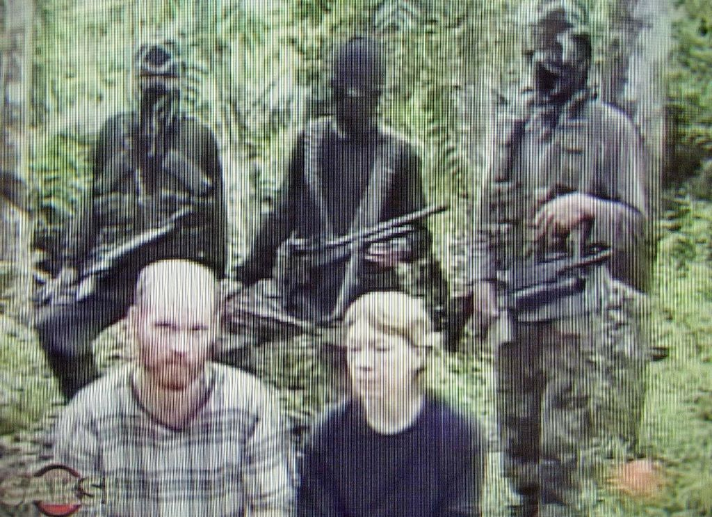 A frame from network broadcasting shows the couple before three gunmen as they read a statement from the Abu Sayyaf.