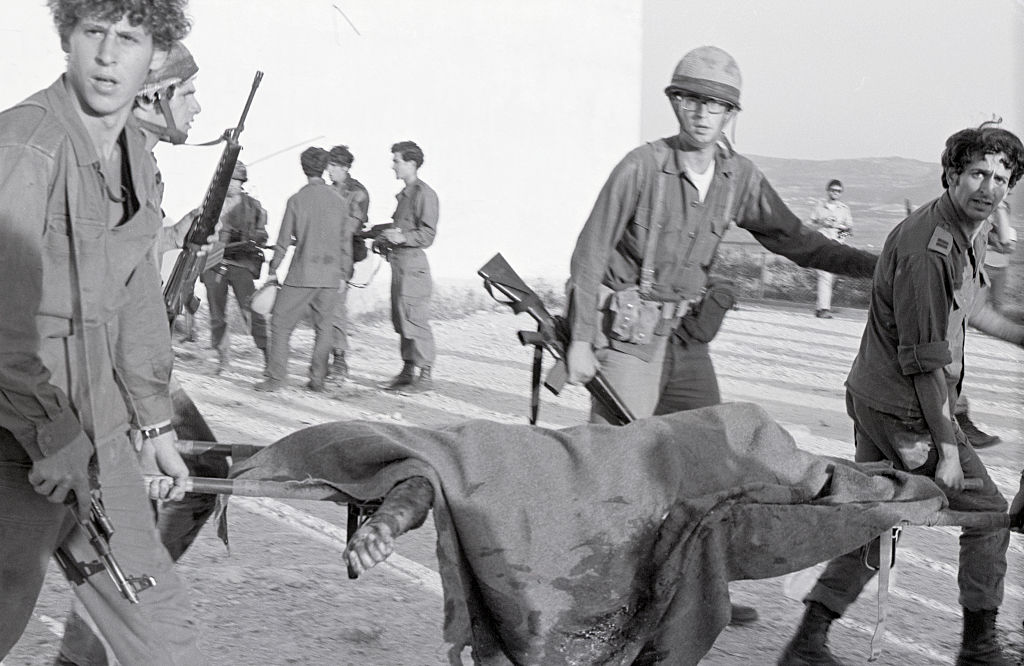 Soldiers carry a dead victim on a stretcher.