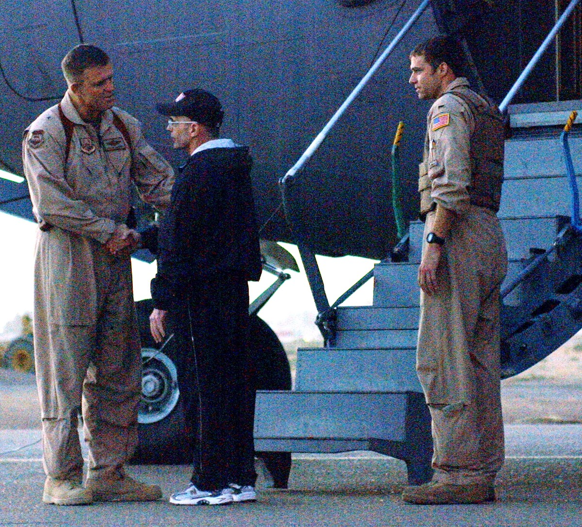 Roy Hallums shakes hands with a US troop in front of the plane that will take him home.