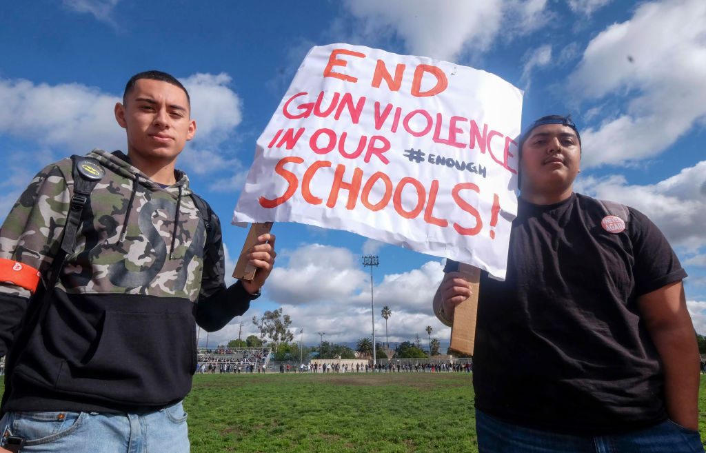 High schoolers hold up a sign to end gun violence in schools.