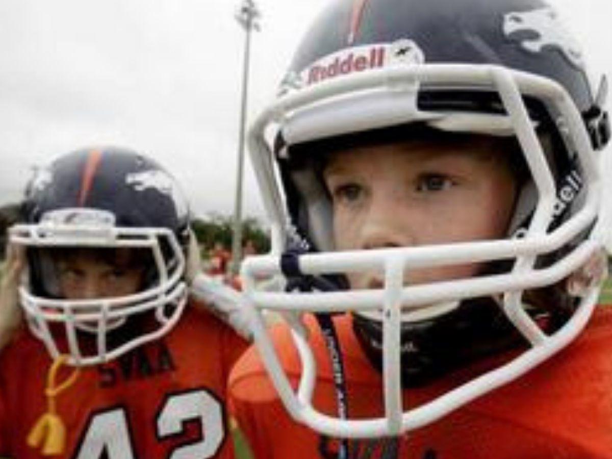 kids in football helmets staring at field