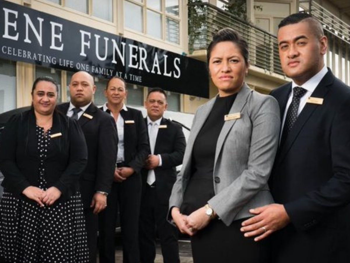 standing in front of funeral home looking serious