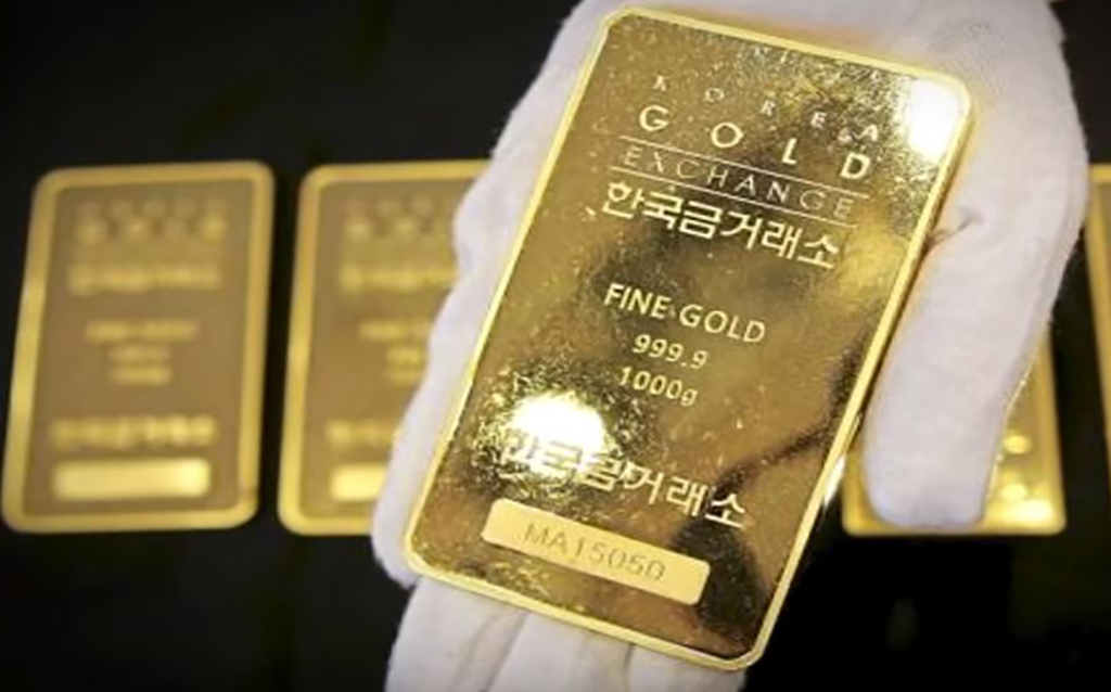 Holding out gold bar with gloved hand