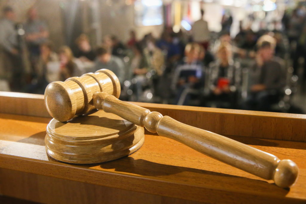 A court gavel rests on a judge's stand