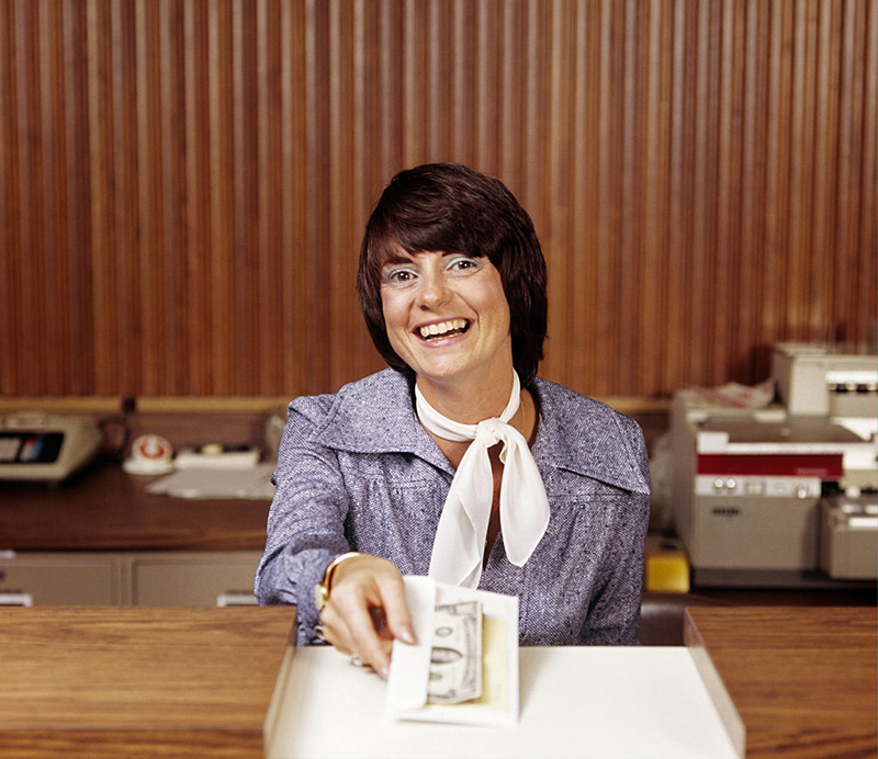 A bank teller hands over money wearing a smile