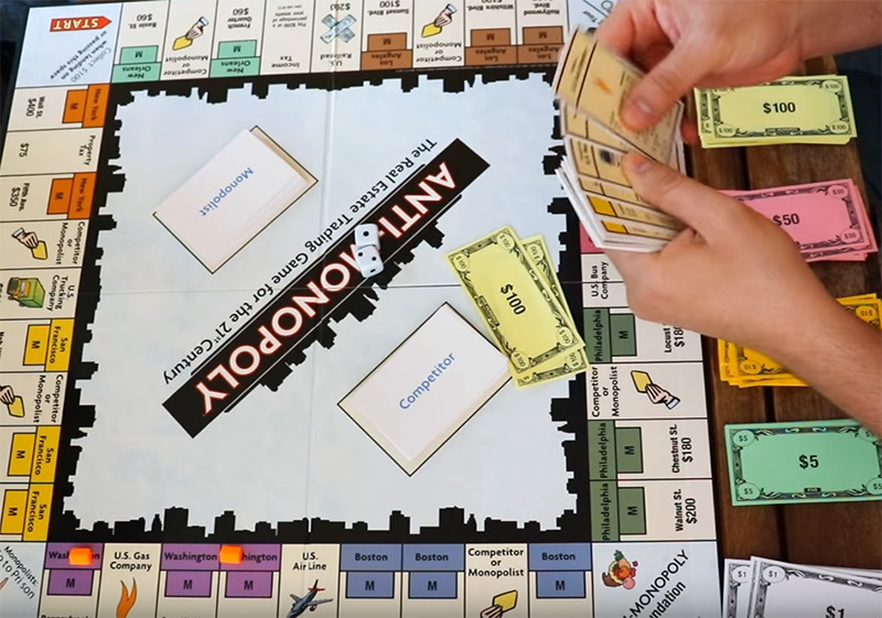 A player shuffles through property cards above the Anti-Monopoly game board