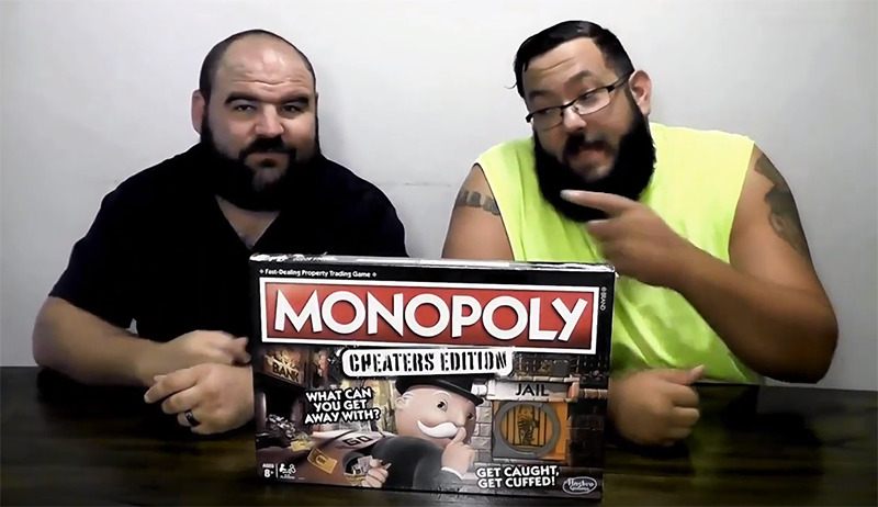 A man points to the man seated beside him as they present Monopoly Cheaters Edition