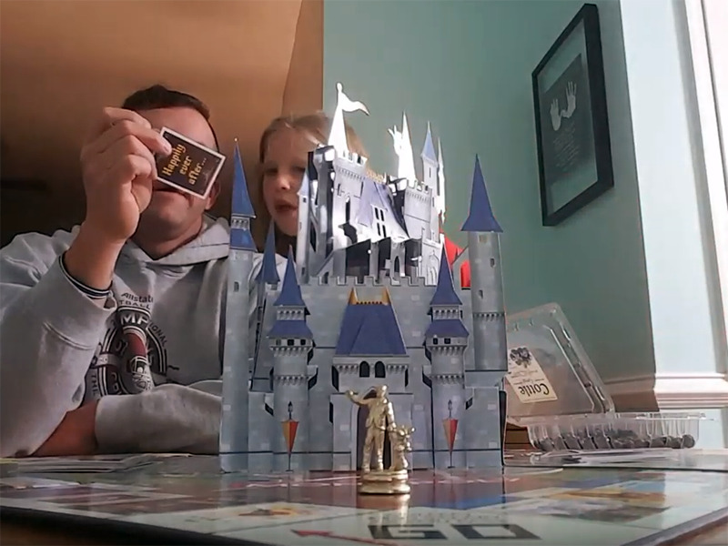 A popup Disney castle centers the Monopoly game a girl and man play