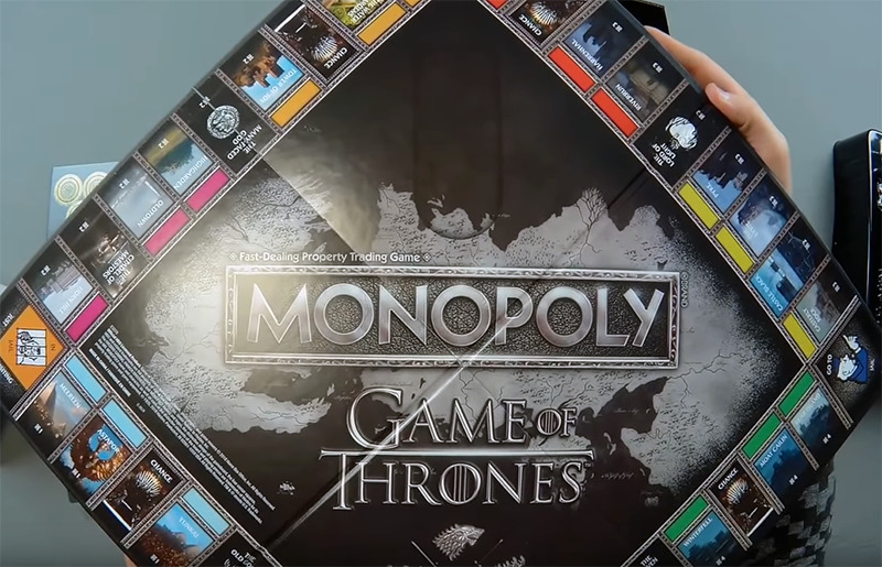 A youtuber holds up the Monopoly Game of Thrones board