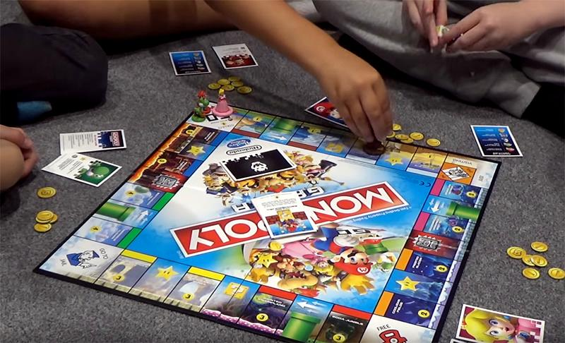 Kids seated on the floor play Monopoly Gamer