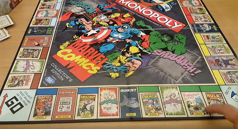A player points to a spot on the Monopoly Marvel Comics Gameboard