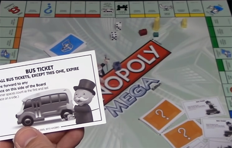 A player shows the card he picked over the Monopoly Mega gameboard