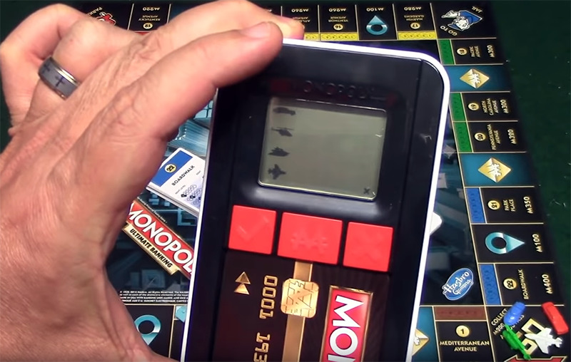 A player holds the Monopoly Ultimate Banking card up to the game's scanner
