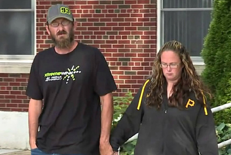 The couple holds hands while exiting jail
