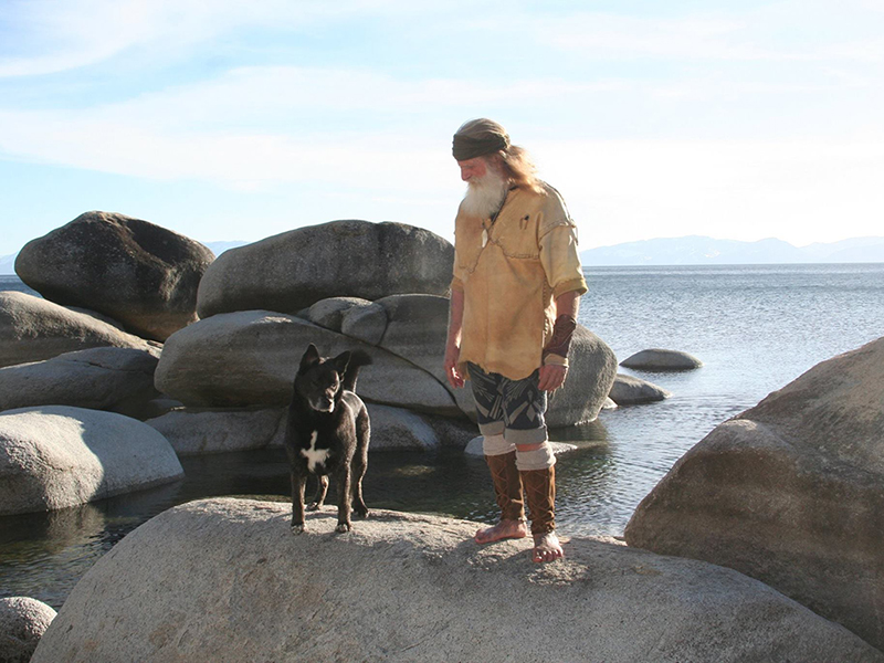 Mick stares at his dog who stands next to him on a rock in the ocean