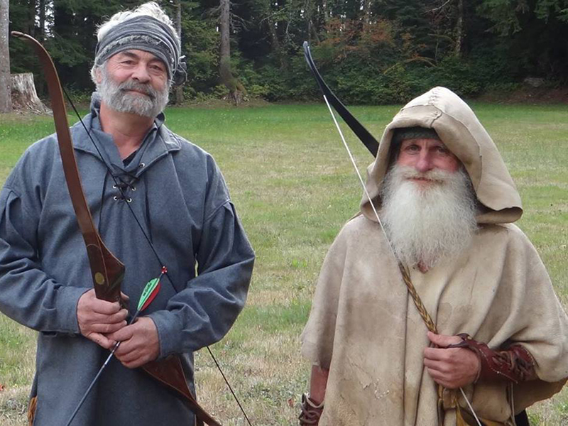 Mick poses next to a friend while holding a bow and arrow