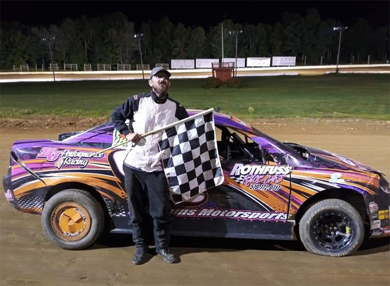 Robert holds a checkered flag in front of a racecar