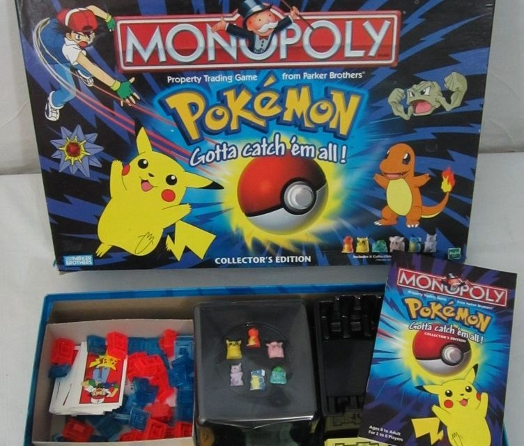 The Monopoly Pokemon lid is removed and revealed the game pieces in the box