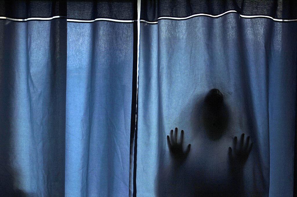 a figure behind a curtain