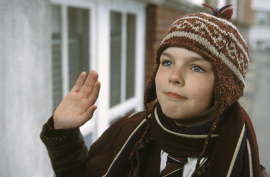 A young boy waves at a doorstep.