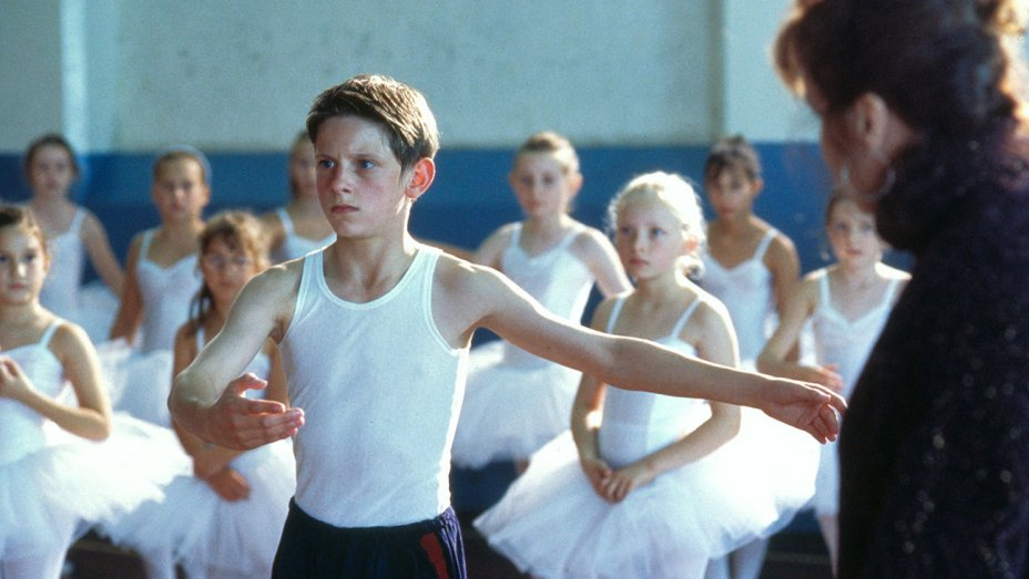 A boy practices ballet in a room full of girls.