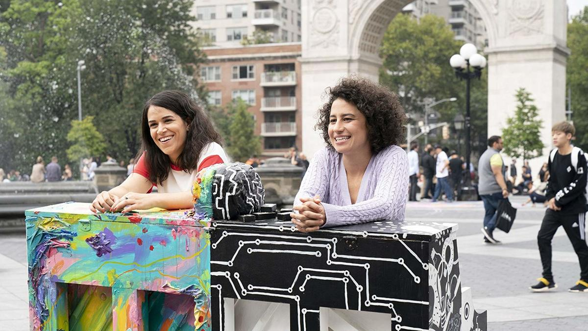 abbi jacobson and ilana glazer standing behind a painted piano in a new york city park