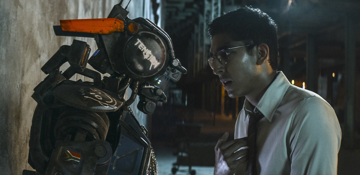 A man looks genuinely at a robot.