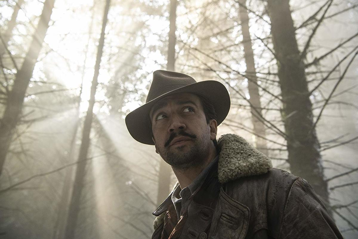 lin-manuel miranda in a leather jacket and hat standing in a sunlit forest