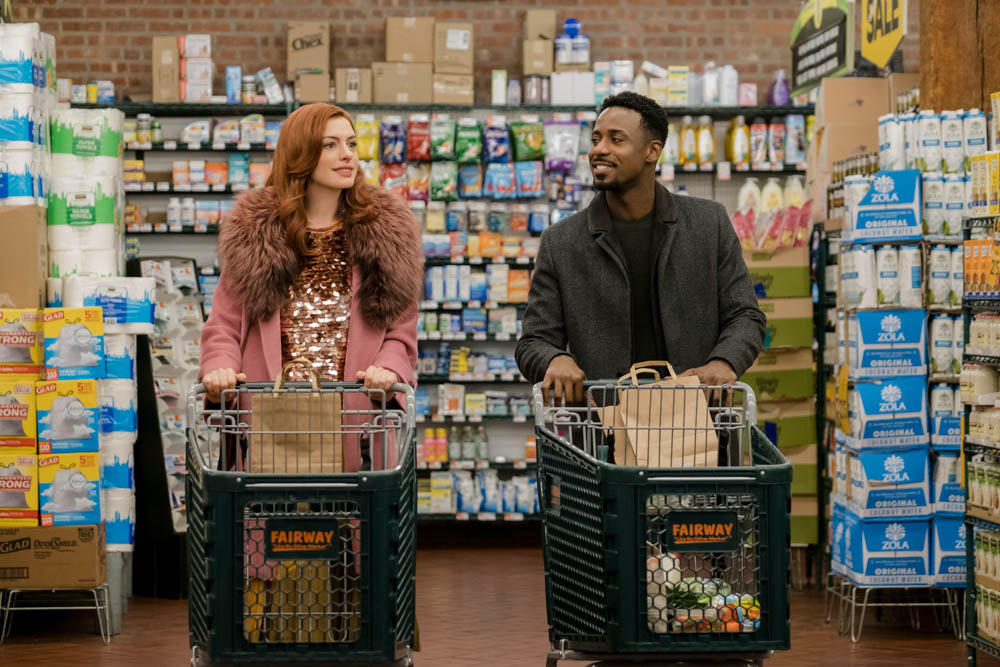 anne hathaway and gary carr pushing shopping carts in a grocery store