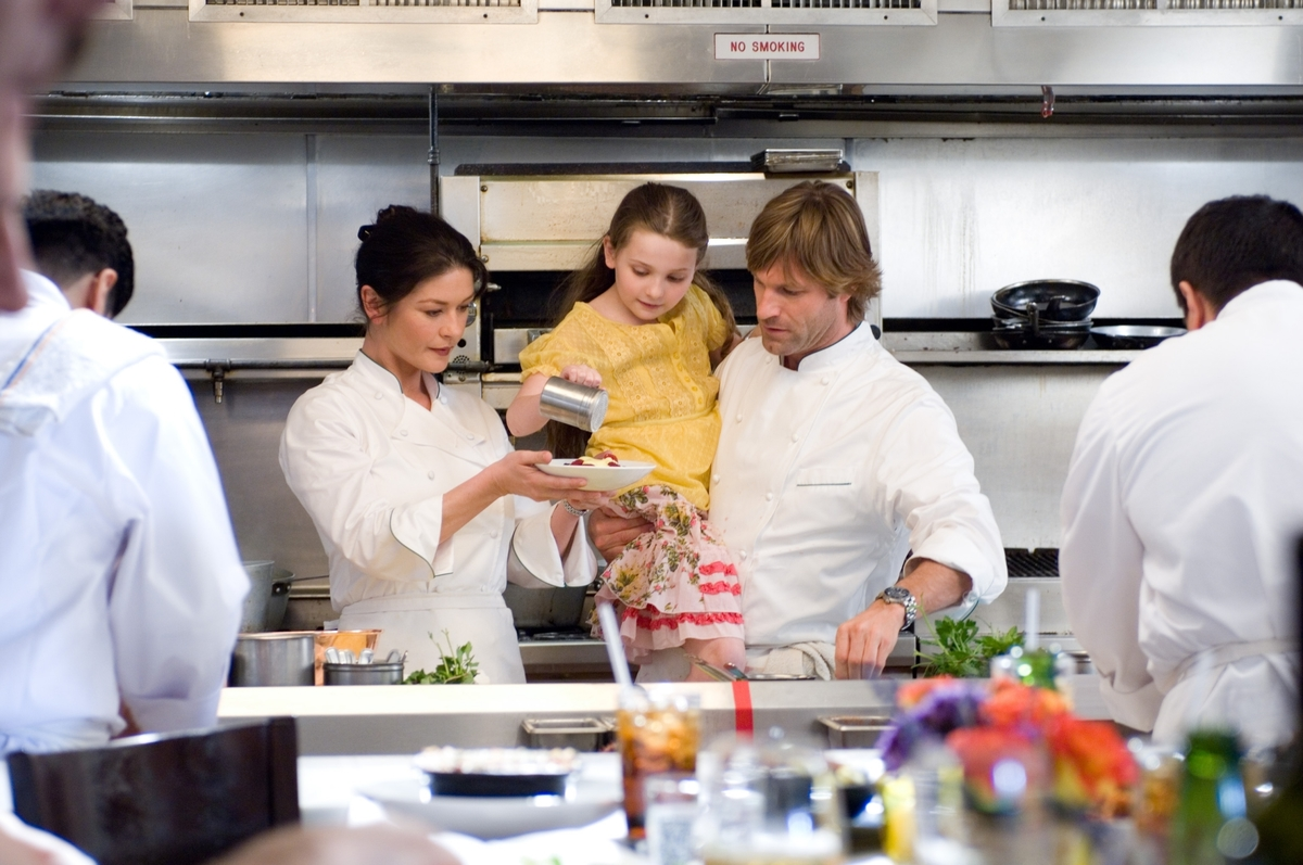 A young girl assists two chefs.