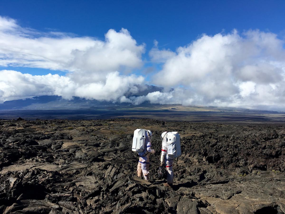 Two astronauts walk on rocky terrain.